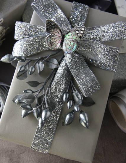 Tie one on: Solid-colored paper (it can be cheap) and sumptuous ribbon are among the secrets gift wrap guru Nickolas Kniel (www. Nicholaskniel.com) shares at his eponymous wrap store in Atlanta. Photo by Jeremy Harwell.   <strong></strong>