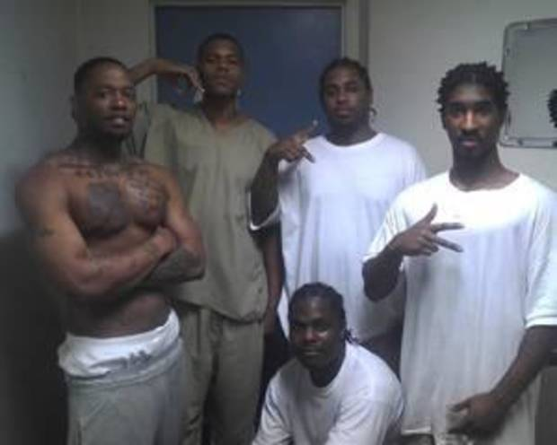 """Oklahoma inmate De'Ontel Harris, squatting, posted this photo in March 2012 to his Facebook page. He refers to himself as """"De'Ontel Savagedagreat Harris."""" Harris, 22, was convicted in 2009 of shooting with intent to kill. He is serving a 10-year sentence at the Davis Correctional Facility in Holdenville. Facebook - Facebook"""