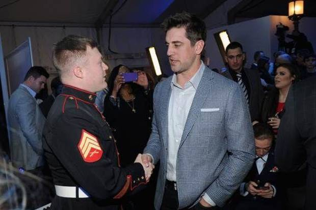 Green Bay Packers quarterback Aaron Rodgers, right, meets a veteran at the event.
