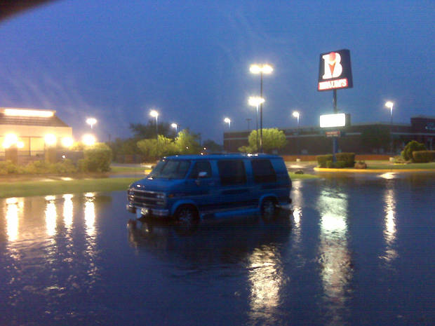 A van stalled with five people in it at NW 62 and N May about 6 a.m. NW 63 and May early Monday morning. A police officer said water was three feet deep in the area. Photo by Robert Medley