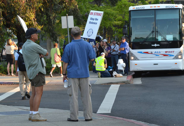 Two BART strikers stand and look towards a long line of commuters working their way down California Boulevard to buses waiting to take them to San Francisco on the second day of the BART strike in Walnut Creek, Calif., on Tuesday, July 2, 2013. (AP Photo/The Contra Costa Times, Dan Rosenstrauch)