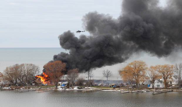 A house burns Monday, Dec. 24, 2012 in Webster, New York. An ex-con set a car and a house ablaze in his lakeside neighborhood to lure firefighters, then opened fire on them, killing two, engaging in a shootout with police and committing suicide while several homes burned. Authorities used an armored vehicle to evacuate the area. (AP Photo/Democrat & Chronicle, Jamie Germano)