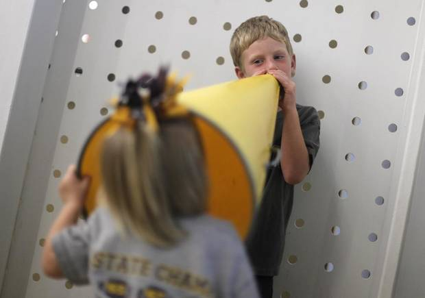 Robert Barnett, 5, and his sister Aislin, 2, of Kingfisher, play with a megaphone before a highs school football game between Heritage Hall and Clinton in Oklahoma City, Friday, Sept. 7, 2012.  Photo by Garett Fisbeck, The Oklahoman
