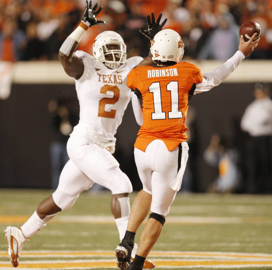 Sergio Kindle (2) of Texas rushes Zac Robinson (11) during the college football game between the Oklahoma State University Cowboys (OSU) and the University of Texas Longhorns (UT) at Boone Pickens Stadium in Stillwater, Okla., Saturday, Oct. 31, 2009. Photo by Doug Hoke, The Oklahoman