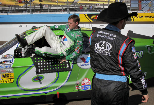 Driver Ricky Stenhouse Jr. climbs out of his car after qualifying for the NASCAR Nationwide Series auto race as driver Austin Dillon looks away, Saturday, Nov. 10, 2012, at Phoenix International Raceway in Avondale, Ariz. (AP Photo/Matt York)