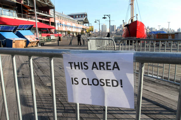 In this Friday, Nov. 23, 2012 photo, barricades close off a section of New York's South Street Seaport. The South Street Seaport, a popular tourist destination, remains a ghost town since Superstorm Sandy. (AP Photo/Tina Fineberg)
