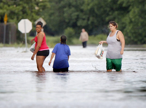 Residents walk away from a flooded mobile home park off of Air Depot Blvd. between NE 10th and NE 23rd St. in Midwest City, OK, Saturday, June 1, 2013, after up to eight inches of rain fell during the previous 24 hours. Photo by Paul Hellstern, The Oklahoman