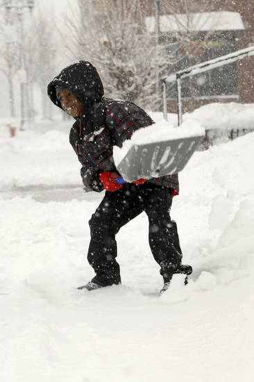 "Seven-year-old Darius McDade shovels snow outside Morningside Baptist Church after services ended on Selby Avenue in St. Paul, Minn., on Sunday, Feb. 10, 2013. While nearby grown-ups around told him he didn't have to shovel, Darius said, ""I saw somebody else shoveling, and I wanted to help."" (AP Photo/Pioneer Press, Ginger Pinson)"