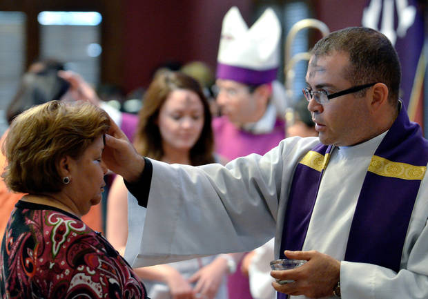 Father Jorge Gomez of Holy Family Church distributes ashes during Ash Wednesday services at the University of Texas at Brownsville and Texas Southmost College on Wednesday, Feb. 22, 2012 in Brownsville, Texas. The practice of placing ashes on one's forehead is a sign of repentance to God and today marks the beginning of the 40 day period of prayer and fasting. (AP Photo/The Brownsville Herald, Paul Chouy)