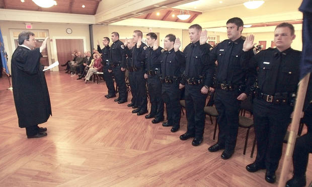 Municipal Judge Alan Synar administers the oath to nine new police officers during the December graduation ceremony for the first Edmond Police Department Basic Police Academy. PHOTO BY PAUL HELLSTERN, OKLAHOMAN ARCHIVE