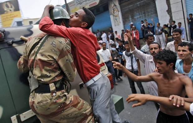 An anti-government protestor kisses a Yemeni army soldier during a demonstration demanding the resignation of Yemeni President Ali Abdullah Saleh, in Taiz,Yemen, Thursday, April 7, 2011. The Yemeni opposition has welcomed an offer by Arab Gulf states to mediate between the president and opposition protesters who have demanded Ail Abdullah Saleh step down after 32 years in power. (AP Photo/Hani Mohammed) ORG XMIT: XMM110