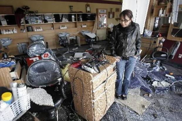 Tornado damage near the intersection of Rockwell and Northwest Expressway, Wednesday , February 11, 2009.  Nieka  Harms looks through her damaged Fantastic Sam's hair salon . By David McDaniel