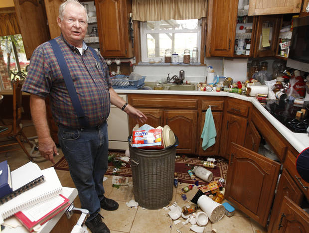 Joe Reneau displays the damage his home received in two earthquakes in less than 24 hours in Sparks, Okla., Sunday, Nov. 6, 2011. Reneau said the trash can at center had been filled with items damaged in an early morning quake on Saturday. The items on the floor and countertops spilled out of the cabinets during a quake on Saturday night. (AP Photo/Sue Ogrocki) ORG XMIT: OKSO111