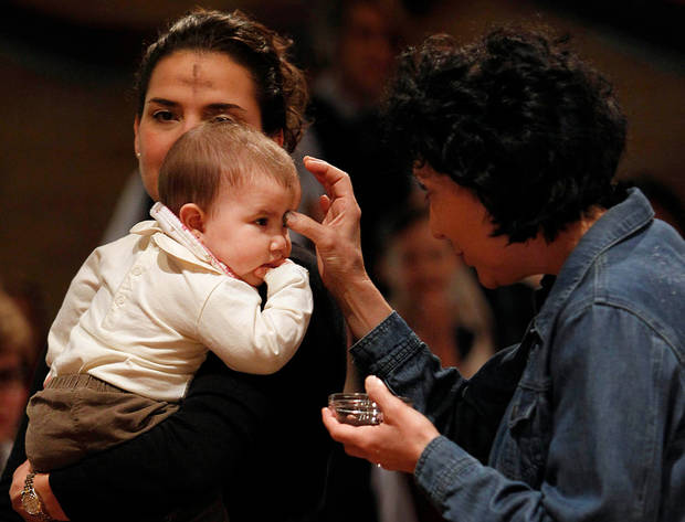 Elisa Salinas holds  her daughter Emelina salinas, 6 month-old, as the family receive ashes from Ann Biro during Ash Wednesday services at Corpus Christi Catholic Church on Wednesday, Feb. 22, 2012, in Houston. (AP Photo/Houston Chronicle, Mayra Beltran)  MANDATORY CREDIT