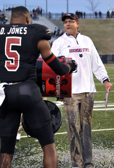 Arkansas State head coach Gus Malzahn reacts after defensive back Don Jones (5) doused him in the last minutes of the Sun Belt Conference NCAA college football game against Middle Tennessee on Saturday, Dec. 1, 2012, in Jonesboro, Ark. Arkansas State won 45-0. (AP Photo/The Jonesboro Sun, Krystin McClellan)
