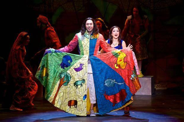 "Joseph, portrayed by Ace Young, shows off his character'™s famous coat of many colors as The Narrator (Diana DeGarmo) looks on in a performance of ""Joseph and the Amazing Technicolor Dreamcoat."" Photo provided"