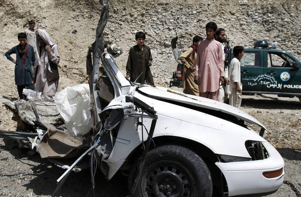Afghans look at the wreckage of a vehicle after a roadside explosion on the outskirts of Laghman province east of Kabul, Afghanistan, Sunday, Aug. 12, 2012. A provincial spokesman says a roadside bomb has killed a district chief in eastern Afghanistan and three of his bodyguards. (AP Photo/Rahmat Gul)