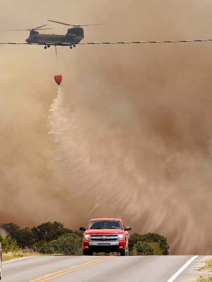 A Helicopter drops water on a large grass fire east of 120th near Cemetery Road on Friday, Aug. 3, 2012, east of Norman, Okla.  Photo by Steve Sisney, The Oklahoman