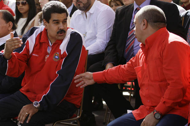Vice President Nicolas Maduro, left, speaks with National Assembly President Diosdado Cabello during a rally outside of Miraflores presidential palace in Caracas, Venezuela, Thursday, Jan. 10, 2013. The government organized the unusual show of support for the cancer-stricken leader on the streets outside Miraflores Palace on what was supposed to be his inauguration day. The government invited leaders from across Latin America and the Caribbean to add political weight to the inauguration without Chavez, while the country's opposition demanded details about Chavez's state and called the delay of the formal swearing-in a violation of the constitution. (AP Photo/ Fernando Llano)