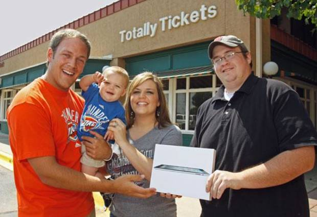 Jared and Whitney Homer and son Tate receive an Ipad from Totally Tickets employee Alex Rames (right) on Tuesday, June 14, 2011, in Norman, Okla.