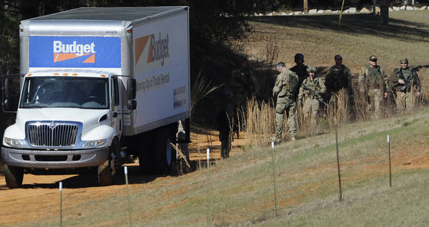 Authorities gather at the Dale County hostage scene in Midland City, Ala. on Thursday morning, Jan. 31, 2013. A gunman holed up in a bunker with a young hostage has kept law officers at bay since the standoff began when he killed a school bus driver and dragged the boy away, authorities said. (AP Photo/Montgomery Advertiser, Mickey Welsh)