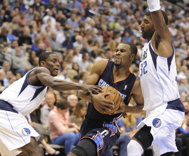 Charlotte Bobcats guard Ramon Sessions, center, drives between Dallas Mavericks guard Darren Collison and guard O.J. Mayo (32) in the first half during an NBA basketball game on Saturday, Nov. 3, 2012, in Dallas. (AP Photo/Matt Strasen)