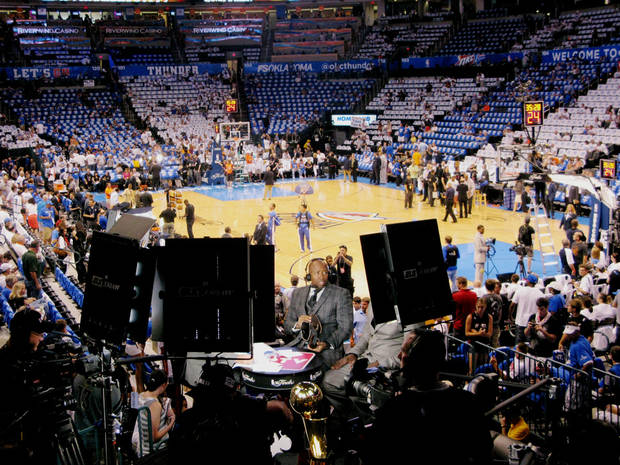 NBA analyst Kenny Smith examines a cowboy boot in front of lights and TV cameras as he discusses Game 2 of the NBA Finals from the Chesapeake Arena for a pregame video to be broadcast on NBA websites. PHOTO BY LILLIE-BETH BRINKMAN, THE OKLAHOMAN. <strong></strong>