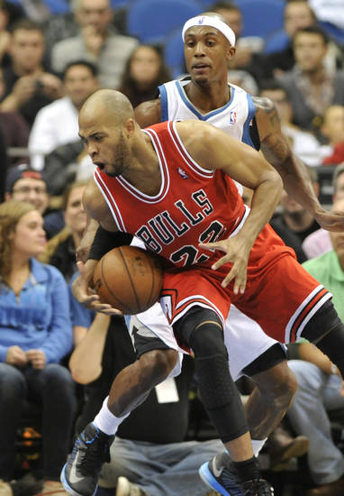 Chicago Bulls' Taj Gibson (22) tries to maintain balance as Minnesota Timberwolves' Dante Cunningham defends during the first half of an NBA preseason basketball game, Saturday, Oct. 13, 2012, in Minneapolis. (AP Photo/Jim Mone)