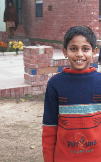 A boy stands outside the Indian orphanage where he lives, the SOS children�s home in Punjab, India. His �mother� is in the background. Read more at blog.NewsOK.com/lindsay-houts.  PHOTO BY LINDSAY HOUTS, THE OKLAHOMAN