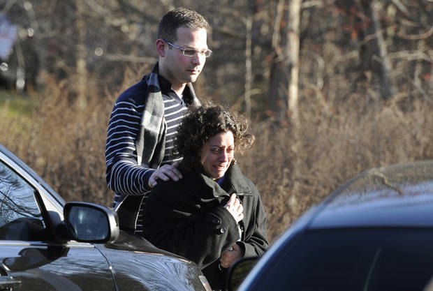 A man and woman leave the staging area for family around near the scene of a shooting at Sandy Hook Elementary School in Newtown, Conn. where authorities say a gunman opened fire, leaving 27 people dead, including 20 children, Friday, Dec. 14, 2012.  (AP Photo/Jessica Hill) ORG XMIT: CTJH108
