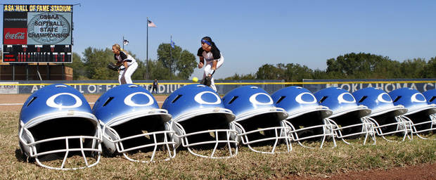 Batting helmets sit along the first base line as Oologah players warm up before their game. Class 4A high school championship softball game between Oologah and Piedmont at Hall of Fame Stadium in Oklahoma City on Saturday, Oct. 15, 2012.  Oologah won the game in the bottom of the sixth inning when Baleigh Hamilton scored the winning run on a hit by Alex Edinger, allowing them to claim the victory by virtue of the the run rule, defeating Piedmont,  10-0.    Photo by Jim Beckel, The Oklahoman