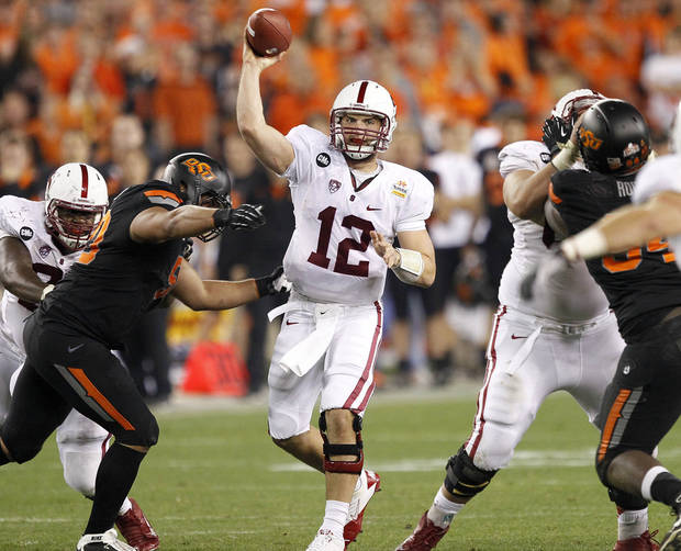 Stanford quarterback Andrew Luck (12) throws under pressure from Oklahoma State defensive end Jamie Blatnick during the second half of the Fiesta Bowl NCAA college football game Monday, Jan. 2, 2012, in Glendale, Ariz. (AP Photo/Matt York)