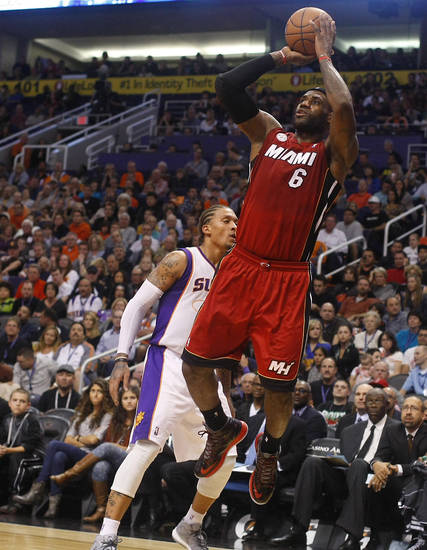 Miami Heat forward LeBron James (6) draws the foul and scores on Phoenix Suns forward Michael Beasley (0) in the second quarter during an NBA basketball game on Saturday, Nov. 17, 2012, in Phoenix. (AP Photos/Rick Scuteri)