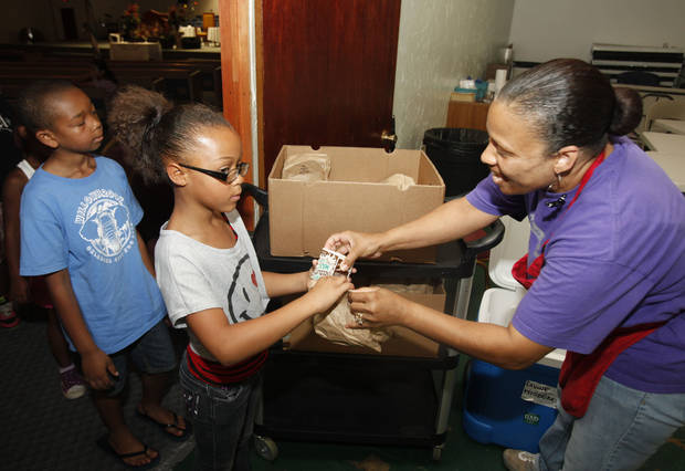Site Director Felicia Manning hands out lunches during a children's summer camp at the Divine Wisdom Worship Center in Midwest City, OK, Thursday, July 19, 2012,  By Paul Hellstern, The Oklahoman