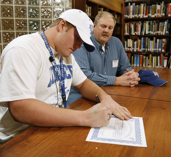 Nathan Badger signs a letter of intent to play college football as his father David watches at Norman North High School in Norman, Okla. on Wednesday, Feb. 4, 2009.    Photo by Steve Sisney, The Oklahoman