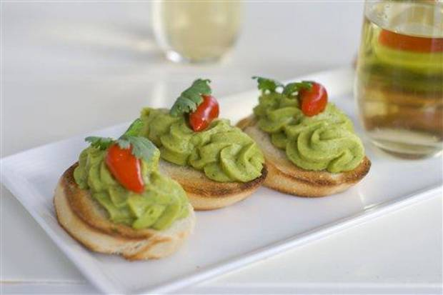 In this image taken on Monday, November 26, 2012, Christmas sangria and spring pea guacamole are shown in Concord, N.H. (AP Photo/Matthew Mead)