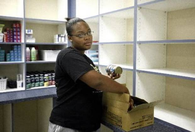 Midwest  City High School junior Meladee Cheadle stocks  food in a  pantry at  Oklahoma Youth Services in  Oklahoma  City, Thursday July, 23, 2009. Photo by Sarah Phipps