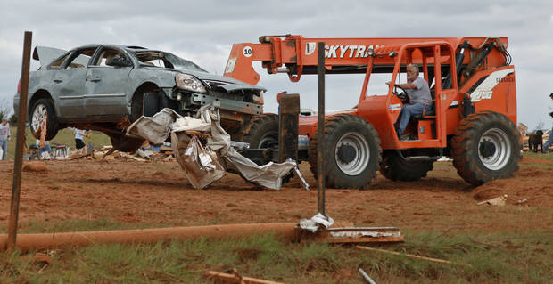 Tornado damaged cars are moved with a lift truck from the home of Jesse and Miranda Lewis west of El Reno, Wednesday, May 25, 2011. Photo by Chris Landsberger, The Oklahoman