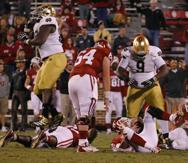 Notre Dame's Kapron Lewis-Moore (89) , left, and Louis Nix III (9) celebrate over OU's Landry Jones (12) after the last play of the game during the college football game between the University of Oklahoma Sooners (OU) and the Notre Dame Fighting Irish at Gaylord Family-Oklahoma Memorial Stadium in Norman, Okla., Saturday, Oct. 27, 2012. Oklahoma lost 30-13. Photo by Bryan Terry, The Oklahoman