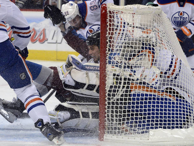 Colorado Avalanche's Patrick Bordeleau , center, shoves Edmonton Oilers goalie Devan Dubnyk, front right, into the goal net on a shot-attempt and gets an interference penalty for the play during the first period of an NHL hockey game in Denver, Saturday, Feb. 13, 2013. The Avalanche won 3-1. (AP Photo/The Denver Post, Andy Cross)  MAGAZINES OUT; TV OUT; INTERNET OUT; NO SALES