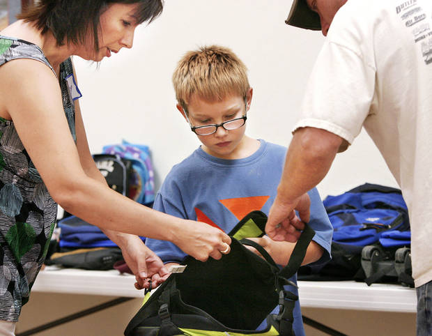 Volunteer Cathy Smith, left, helps Blake Prescott check out a new backpack at the Eastside Church of Christ in Midwest City during the annual back-to-school giveaway.   OKLAHOMAN ARCHIVE PHOTO BY JIM BECKEL