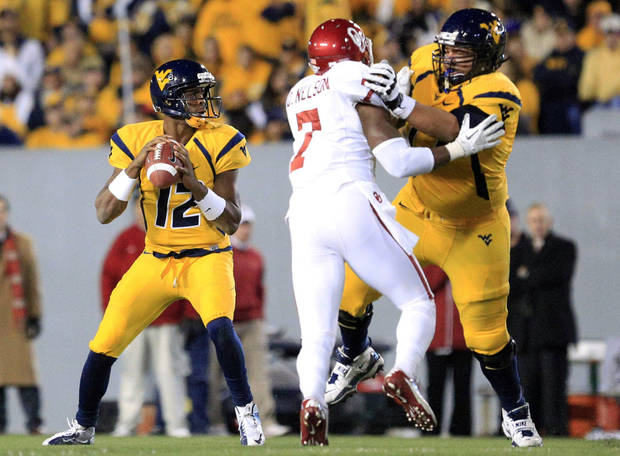 West Virginia quarterback Geno Smith (12) looks to pass as West Virginia's Curtis Feigt (62) blocks Oklahoma's Corey Nelson (7) during the second quarter of their NCAA college football game in Morgantown, W.Va., on Saturday, Nov. 17, 2012. (AP Photo/Christopher Jackson)