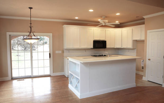 Left: The foreclosed house at 8012 NE 140 features an open kitchen with large island and French doors to the outside from the dining area.  Photo by David McDaniel, The Oklahoman