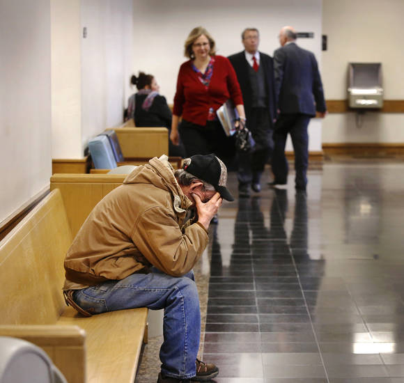 Attorneys scurry back and forth through hallways while a lone man sits outside a courtroom waiting to be called to tell his story at Workers Compensation Court in the Denver Davison Building near the state Capitol on Thursday,  Feb. 21, 2013.   Photo by Jim Beckel, The Oklahoman