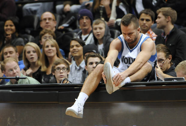 Minnesota Timberwolves' Jose J.J. Barea ties his shoe after he wound up on the scorer and press table chasing a loose ball in the first half of an NBA basketball game against the Orlando Magic Wednesday, Nov. 7, 2012, in Minneapolis. The Timberwolves won 90-75. (AP Photo/Jim Mone)