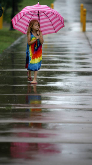 Amelie Paugh, 5, walks under a umbrella during the LibertyFest's ParkFest at the University of Central Oklahoma, Sunday, July 4, 2010, in Edmond, Okla. Photo by Sarah Phipps, The Oklahoman