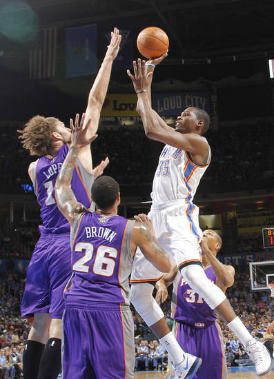 Oklahoma City Thunder small forward Kevin Durant (35) shoots the ball overPhoenix Suns center Robin Lopez (15) and Phoenix Suns shooting guard Shannon Brown (26) during the NBA basketball game between the Oklahoma City Thunder and the Phoenix Suns at the Chesapeake Energy Arena on Wednesday, March 7, 2012 in Oklahoma City, Okla.  Photo by Chris Landsberger, The Oklahoman