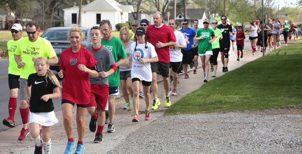 Runners of all ages, many wearing red socks in honor of the Boston Marathon bombing victims, ran through Edmond Monday in what was called a Boston Strong Run. PHOTO BY DAVID MCDANIEL, THE OKLAHOMAN. <strong>David McDaniel - THE OKLAHOMAN</strong>