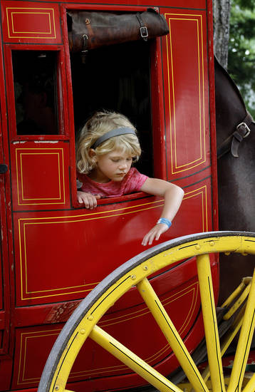 A inquisitive young girl (unidentified) leans through a stagecoach window to touch the large wooden wheel before the wagon ride begins. The Chuckwagon Gathering and Children's Cowboy Festival returned to the National Cowboy & Western Heritage Museum in Oklahoma City for its 22nd year this weekend. Boys and girls dressed in cowboy duds to participate in a wide array of activities that included stagecoach and covered wagon rides, pony rides, chuckwagon cooking demonstrations, the chance to sample food prepared in Dutch ovens, rope making, face painting, storytelling, musical entertainment and an Old-West Medicine Show at this year's event on Saturday, May 26, 2012.     Photo By Jim Beckel , The Oklahoman