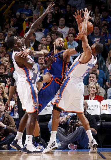 Oklahoma City's Kendrick Perkins (5) and Thabo Sefolosha (2) defend New York's Tyson Chandler (6) during the NBA game between the Oklahoma City Thunder and the New York Knicks at Chesapeake Energy Arena in Oklahoma CIty, Saturday, Jan. 14, 2012. Photo by Bryan Terry, The Oklahoman